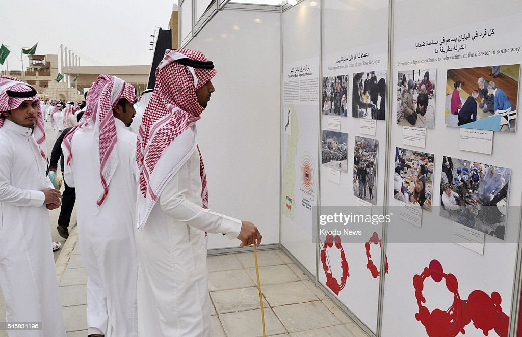 RIYADH Saudi Arabia Men look at a photo exhibit on the March 11 earthquake and tsunami disaster in Japan at an exposition site in a suburb of Riyadh...