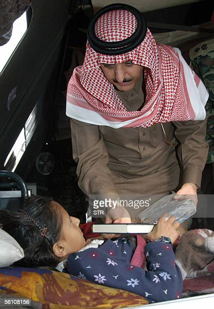 Saudi Arabia Prince Ahmed Bin Abdul Aziz Al Saud presents a Holy Bookand some dates to an injured earthquake survivor girl during his visit to a...