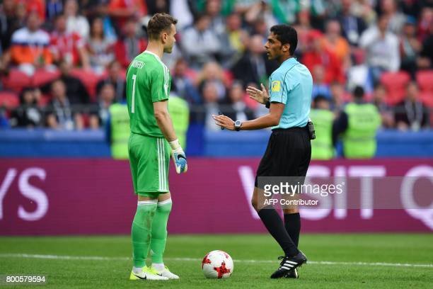 Saudi Arabia referee Fahad alMirdasi speaks to Russia's goalkeeper Igor Akinfeev to explain a goal by Mexico has been eliminated stands by during the...