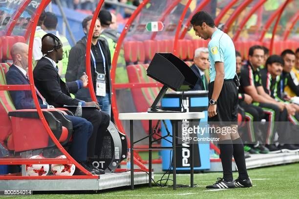 Saudi Arabian assistant Referee 2 Mohammed alAbakry check the video playback during the 2017 Confederations Cup group A football match between Mexico...