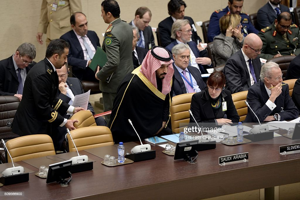 Saudi Arabian Defence Minister Prince Salman Bin Abdulaziz (C) prepares to take his seat as he arrives for the Global Coalition meeting against The Islamic State group IS, held at NATO headquarter in Brussels on February 11, 2016, as Slovenia's Defence Minister Andreja Katic (2-R) and Spanish Defence Minister Pedro Morenes Eulate (R)look on. / AFP / THIERRY CHARLIER