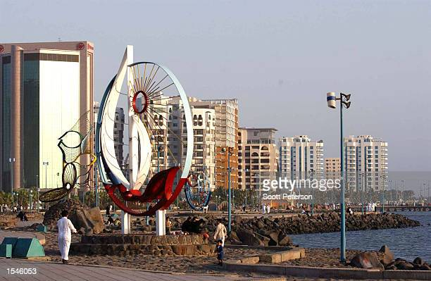 Saudi Arabians look at a public sculpture along the beach May 20 2002 in Jeddah Saudi Arabia Strictly conservative rules for social contact between...