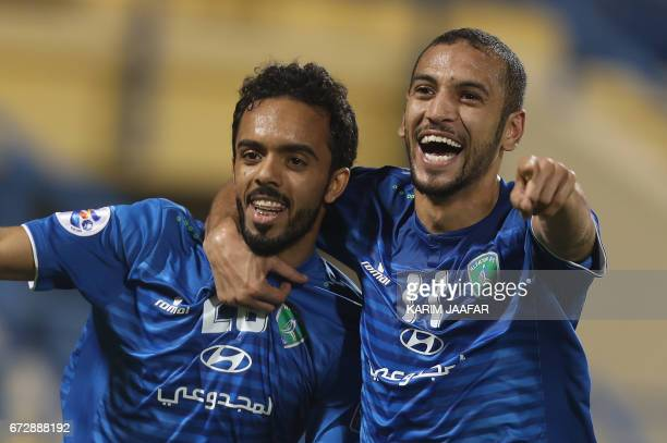 Saudi Arabia's AlFateh FC midfielder Ali Ahmed AlZaqan celebrates with his teammate Hamad Saud Aljuhaim after scoring a goal during the AFC Champions...