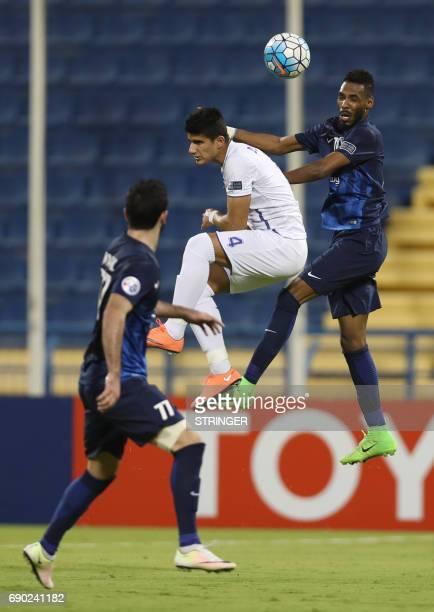 Saudi Arabia's AlHilal defender Mohamed Jahfali and Iran's Esteghlal Khouzestan defender Danial Mahini jump for the ball during the AFC Champions...