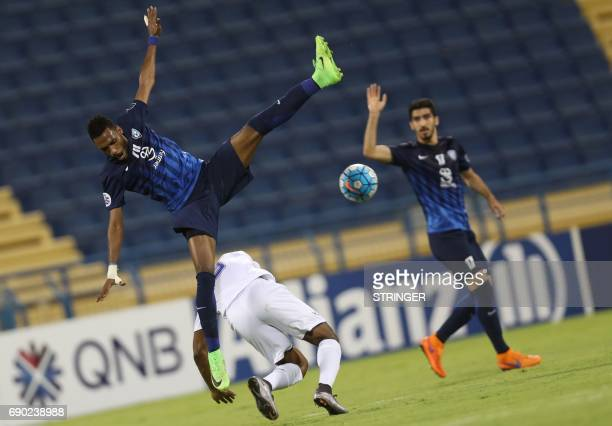 Saudi Arabia's AlHilal defender Mohamed Jahfali jumps in the air as he is tackled Iran's Esteghlal Khouzestan forward Aloys Nong during the AFC...