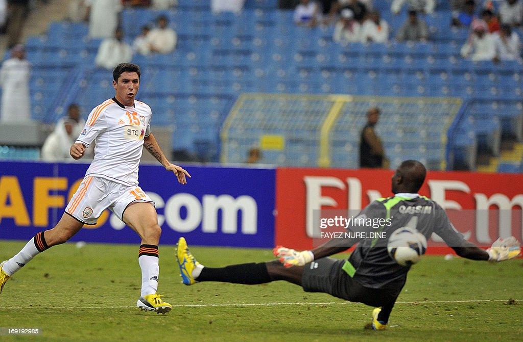 Saudi Arabia's al-Shabab player Sebastian Tagliabue (L) scores against Qatari Al Gharafa goalkeeper Qasem Burhan during their AFC Champions League football match at King Fahad International stadium in Riyadh, on May 21, 2013.