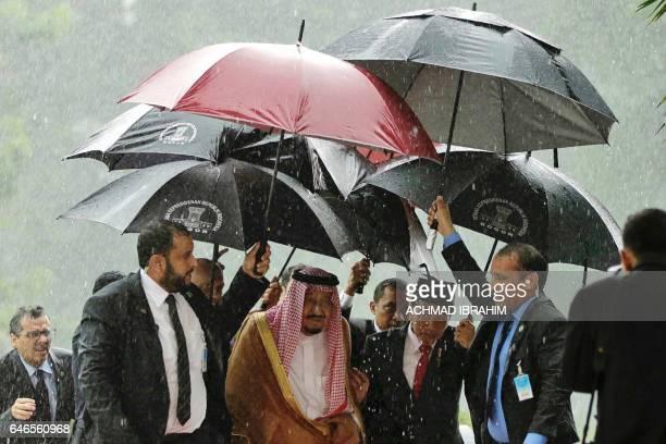 TOPSHOT Saudi Arabia's King Salman bin Abdul Aziz and Indonesia's President Joko Widodo walk in heavy rain at the presidential palace in Bogor West...