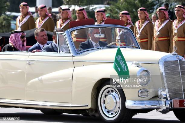 Saudi Arabia's King Salman bin Abdulaziz alSaud and Jordanian King Abdullah II sit in a vintage car during a welcome ceremony at the airport in the...
