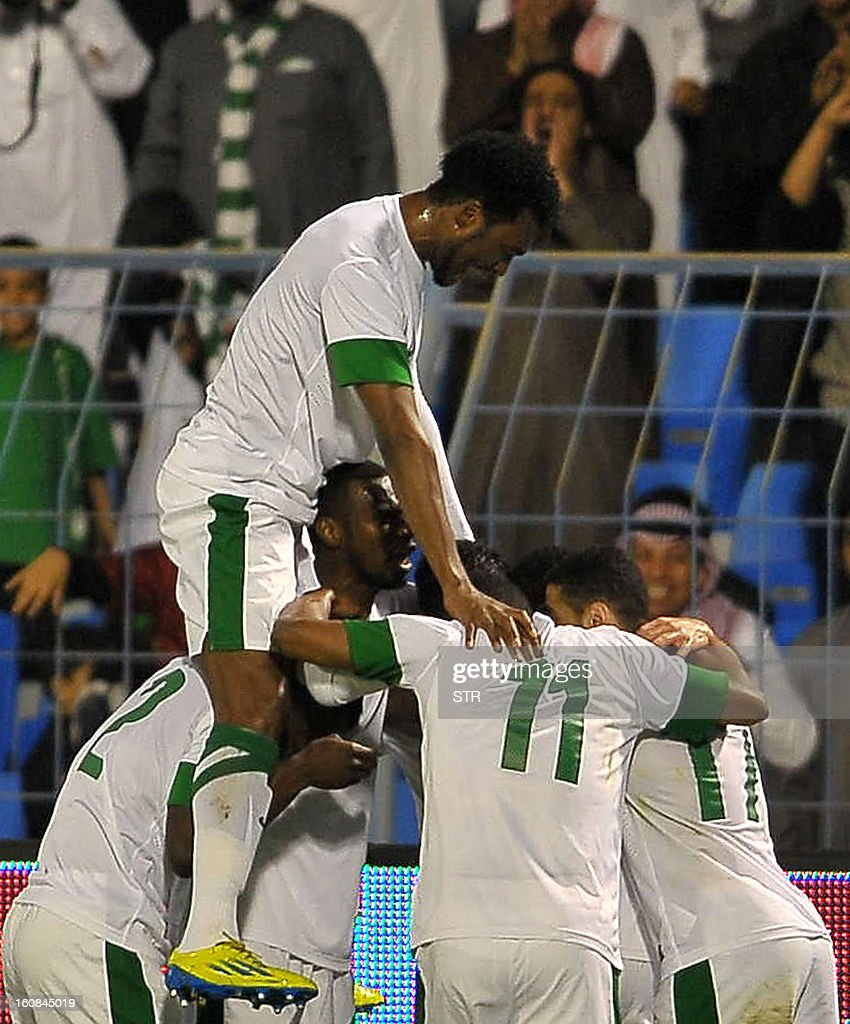 Saudi Arabia's players celebrate after scoring against China during the 2014 World Cup Asian zone qualifying football match between Saudi Arabia and China in Dammam on February 7, 2013. STR