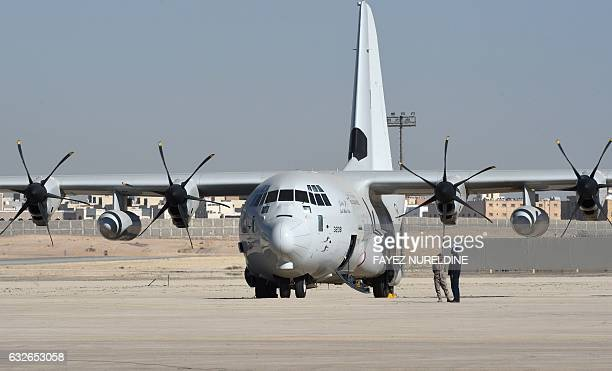 Saudi army officers stand next to a C130 Hercules during a ceremony marking the 50th anniversary of the creation of the King Faisal Air Academy at...