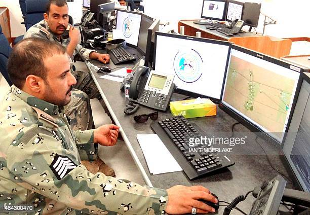 Saudi border guards monitor cameras and radars on surveillance screens of the Saudi northern border with Iraq at Arar regional command and control...