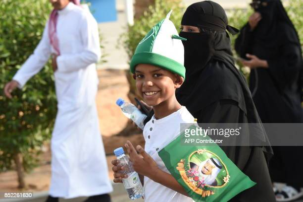 A Saudi boy flashes the victory gesture while carrying a flag bearing the image of the king as he arrives outside a stadium to attend an event in the...