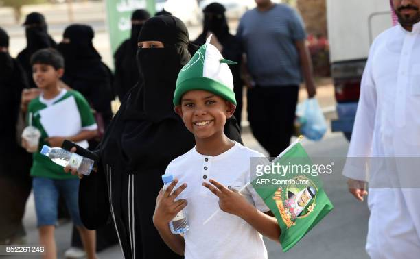 A Saudi boy flashes the victory gesture with both his hands while carrying a flag bearing the image of the king as he arrives outside a stadium to...