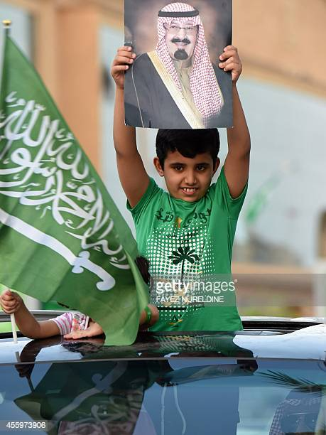 A Saudi boy raises up a portrait of King Abdullah bin Abdulazziz during celebrations marking the 84th Saudi Arabian National Day in the desert...