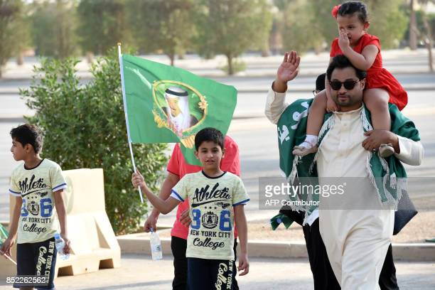 A Saudi boy waves a flag bearing the image of the king as he arrives with his family outside a stadium to attend an event in the capital Riyadh on...