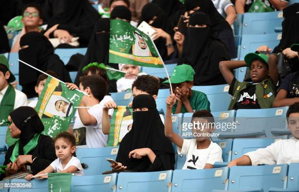 A Saudi boy waves a flag bearing the image of the king as he sits in a stadium to attend an event in the capital Riyadh on September 23 2017...