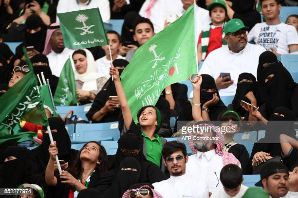 A Saudi boy waves a flag bearing the kingdom's emblem and with a caption reading in Arabic 'the nation is in our hearts' as he sits with other...