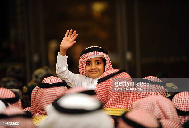 A Saudi boy waves as he waits along the others outside the Masmak Palace to show allegiance to the kingdom's new Crown Prince Salman bin Abdulaziz...