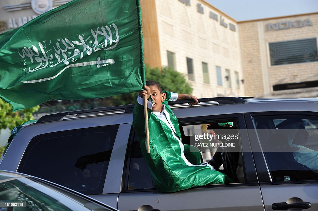 A Saudi boy waves the national flag during celebrations marking the 83rd Saudi Arabian National Day in the desert kingdom's capital Riyadh, on September 23, 2013.