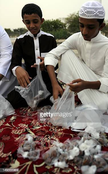 Saudi boys prepare bags containing food and drink to distribute to those who are unable to reach somewhere to eat for breakfast before the start of...