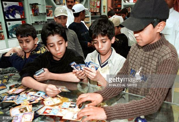 Saudi boys rush to buy the last Pokemon cards available in a Riyadh toy shop 31 March 2001 before Pokemon games in Saudi Arabia will be confiscated...