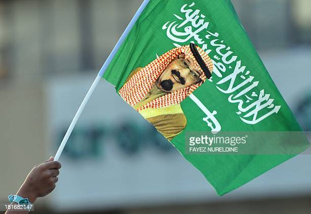 A Saudi child holds up a national flag with picture of King Abdullah bin Abdulaziz during celebrations marking the 83rd Saudi Arabian National Day in...