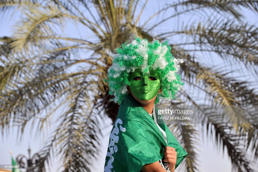 A Saudi child wears a wig and mask in the colours of the national flag during celebrations marking the 83rd Saudi Arabian National Day in the desert kingdom's capital Riyadh, on September 23, 2013.
