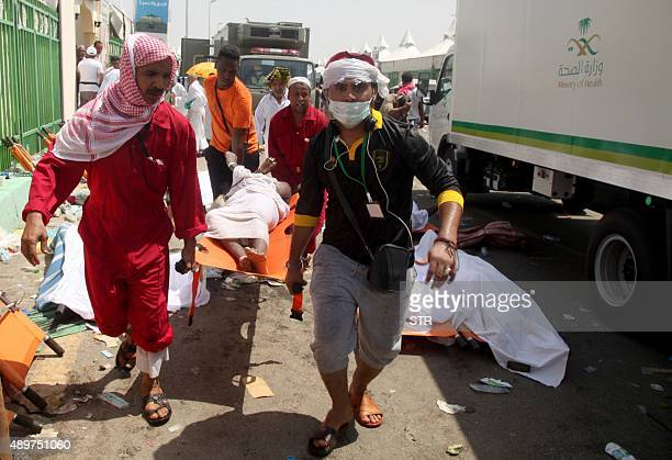 Saudi emergency personnel and Hajj pilgrims carry a wounded person at the site where at least 450 were killed and hundreds wounded in a stampede in...