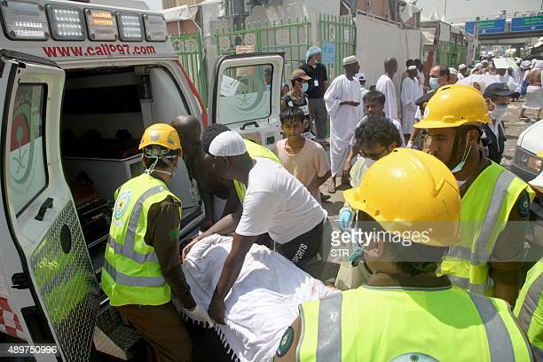 Saudi emergency personnel and Hajj pilgrims load a wounded person into an ambulance at the site where at least 450 were killed and hundreds wounded...