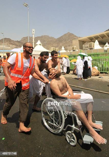 Saudi emergency personnel and Hajj pilgrims push a wounded person in a wheelchair at the site where at least 450 were killed and hundreds wounded in...