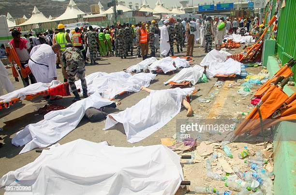 Saudi emergency personnel and Hajj pilgrims stand near bodies covered in sheets at the site where at least 450 were killed and hundreds wounded in a...