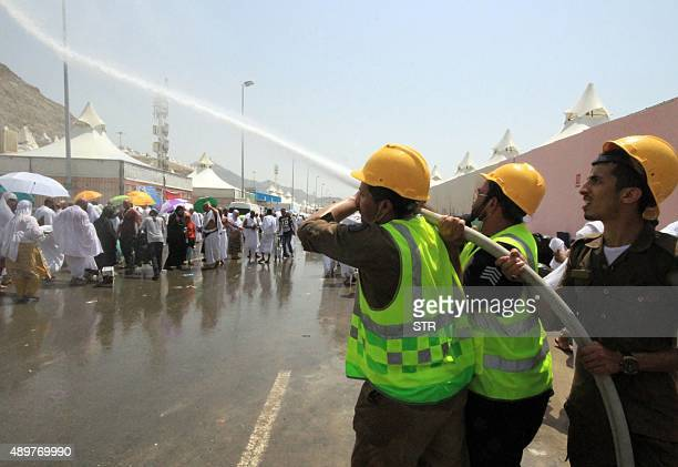Saudi emergency personnel spray water to cool down Hajj pilgrims at the site where at least 450 were killed and hundreds wounded in a stampede in...