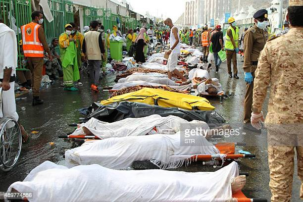 Saudi emergency personnel stand near bodies of Hajj pilgrims at the site where at least 717 were killed and hundreds wounded in a stampede in Mina...