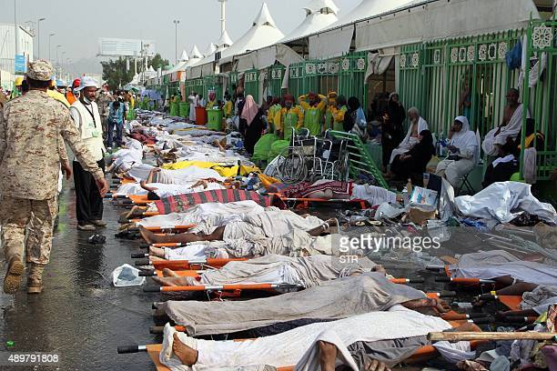 CONTENT Saudi emergency personnel stand near bodies of Hajj pilgrims at the site where at least 717 were killed and hundreds wounded in a stampede in...