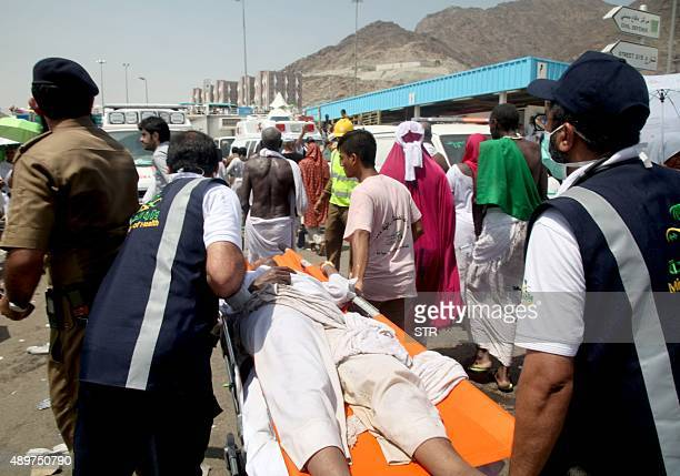 Saudi emergency personnel transport a Hajj pilgim on a stretcher at the site where at least 450 were killed and hundreds wounded in a stampede in...