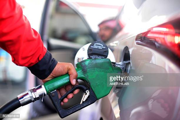 A Saudi employee fills the tank of his car with petrol at a station on December 28 2015 in the Red Sea city of Jeddah Saudi Arabia said it plans to...