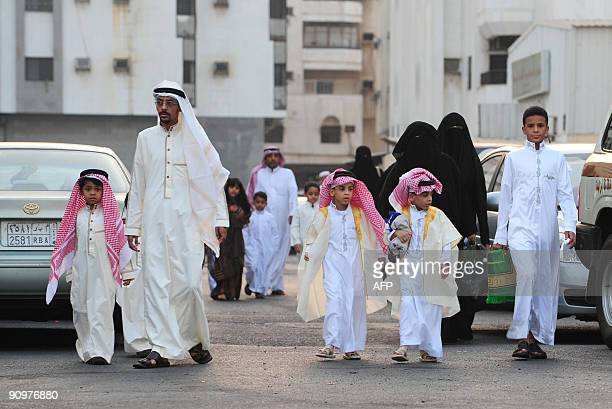Saudi families arrive to the early morning Eid alFitr prayer outside a packed mosque in the Red Sea port of Jeddah on September 20 2009 Most Mulsim...