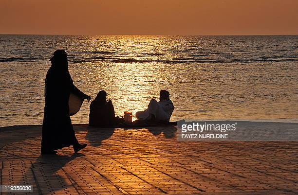 Saudi families spend an evening by a seafront promenade as the sun sets in the Red Sea city of Jeddah on July 7 2011 AFP PHOTO/FAYEZ NURELDINE