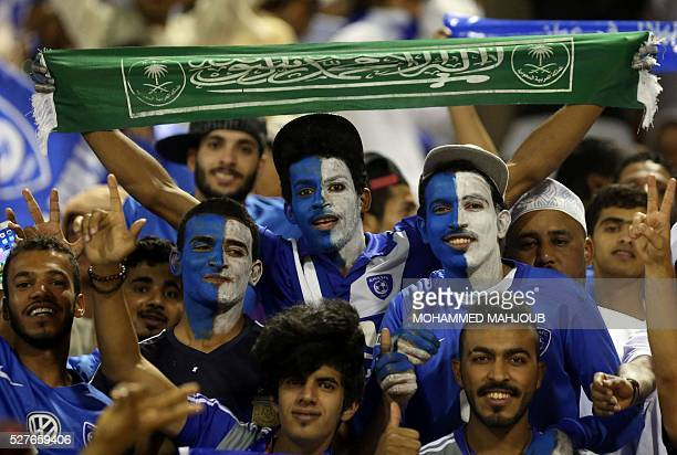 Saudi fans cheer on their team during AlHilal's Asian Champions League group C football match against Iranian club Tractorsazi at the Sultan Qabous...