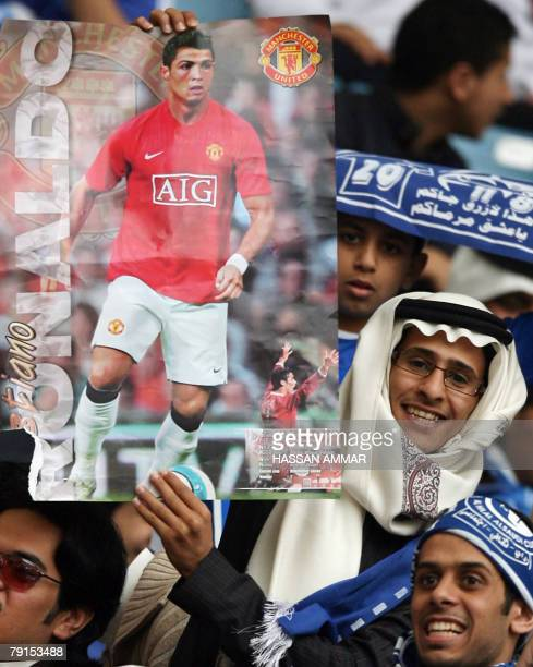 Saudi fans hold a poster of Manchester United player Cristiano Ronaldo prior to a football match between Manchester United and Saudi club alHilal at...