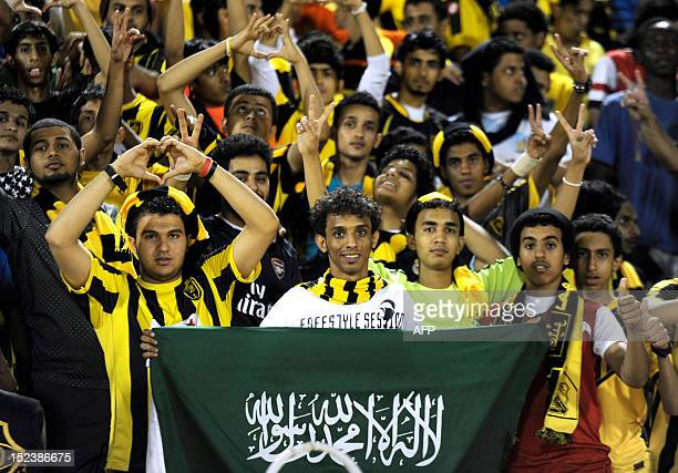 Saudi fans hold up their national flag as they cheer AlIttihad club during their AFC Champions League quarterfinal football match against Guangzhou...