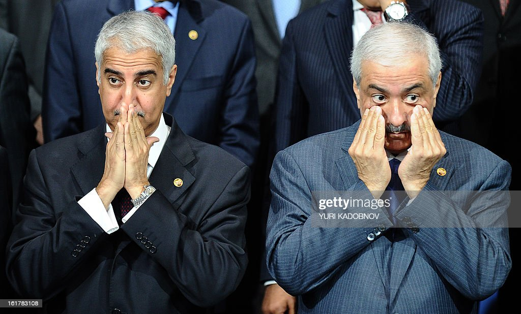 Saudi Finance Minister Ibrahim al-Assaf (R) and Bank Governor Fahad Al-Mubarak (L) touch their faces as they pose for family picture after a meeting of G20 states finance ministers and central bank governors in Moscow, on February 16, 2013. The ministers and central bank governors gathered today in Moscow for their first meeting in the Russian capital aimed at reassuring markets that the world's economic powers would not slug it out in 'currency wars' to boost national growth. AFP HOTO/YURI KADOBNOV