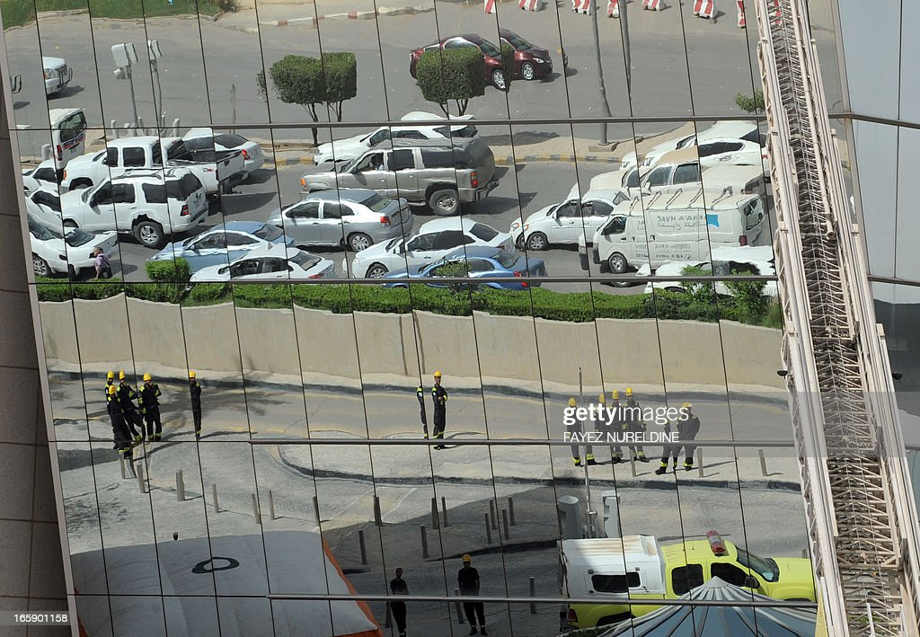 Saudi firefighters and vehicles are reflected in the building glass during a wide civil defence training at the mall of the Mamlaka tower in the center of Riyadh, on April 7, 2013. Saudi authorities carried out several fire extinguisher trainings in huge malls in Riyadh in anticipation of the outbreak of fires as a result of terrorist or criminal acts.