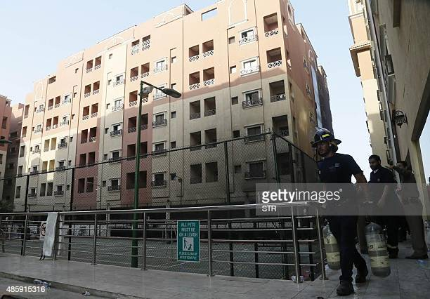 Saudi firefighters walk in a residential complex housing employees of oil giant Saudi Aramco after a fire broke out in it killing 11 people and...