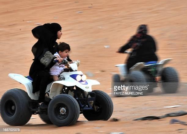 A Saudi girl drives an ATV with a younger sister at Thumamah Park near Riyadh on April 5 2013 Saudi Arabia's religious police have lifted a ban on...