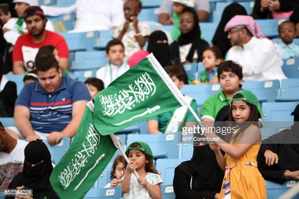 A Saudi girl waves a national flag as she stands by her seat in a stadium attending an event in the capital Riyadh on September 23 2017 commemorating...
