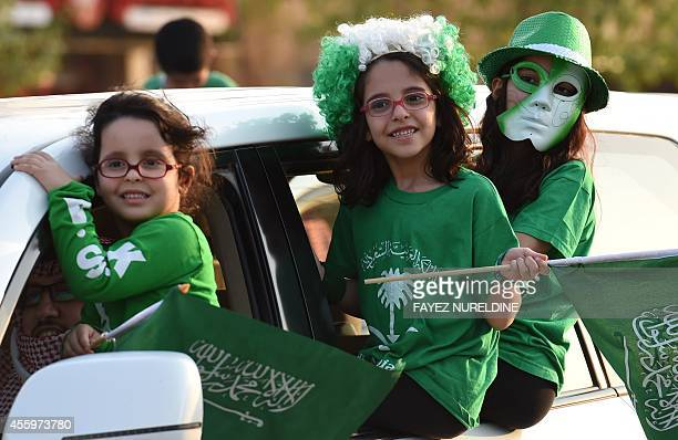 Saudi girls wave national flags during celebrations marking the 84th Saudi Arabian National Day in the desert kingdom's capital Riyadh on September...