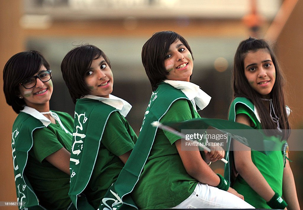 Saudi girls wear the national flag across their shoulders during celebrations marking the 83rd Saudi Arabian National Day in the desert kingdom's capital Riyadh, on September 23, 2013.
