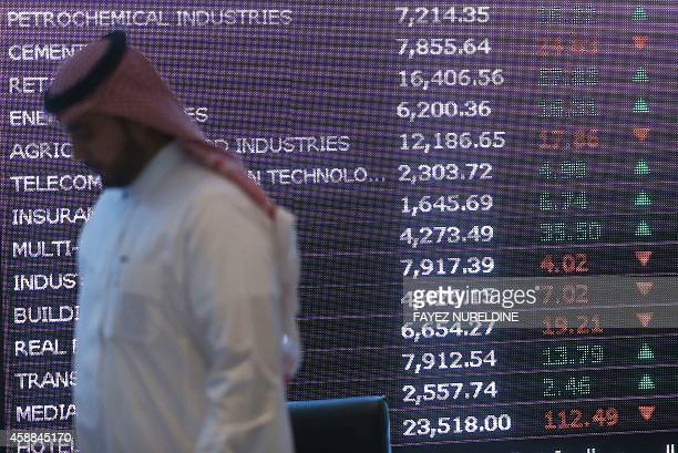 A Saudi investor walks past a screen at the newly opened exchange market department at the National Commercial Bank in Riyadh on November 12 2014 NCB...
