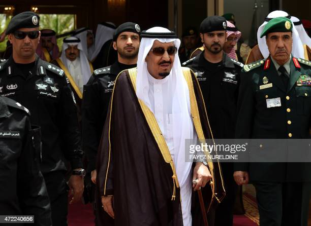 Saudi King Salman bin Abdulaziz walks surrounded by security officers to receive Bahraini King Hamad bin Isa alKhalifa upon the latter's arrival in...